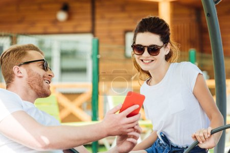 handsome young man showing smartphone to girlfriend