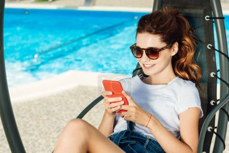 happy young woman using smartphone while relaxing on sun lounger in front of swimming pool