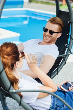 young couple in white t-shirts flirting in front of swimming pool