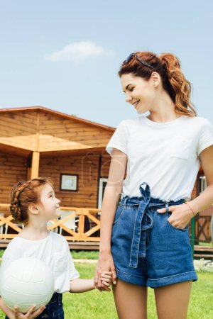 mother and daughter with volleyball ball in white t-shirts in front of wooden cottage