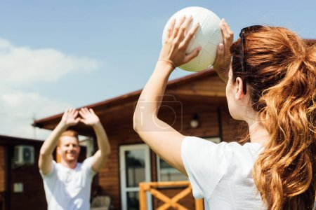 young couple playing volleyball on cottage yard