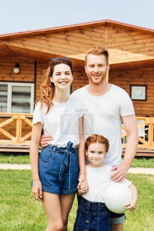 happy young family with volleyball ball standing in front of wooden cottage