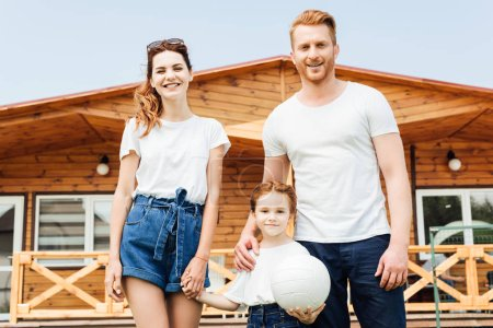 beautiful young family with volleyball ball standing in front of wooden cottage