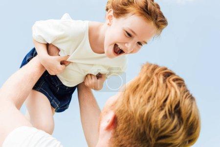 Photo pour Le père joue avec une fille heureuse et jetant son haut - image libre de droit