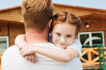 Photo for Rear view of father embracing his adorable little daughter while she looking at camera - Royalty Free Image