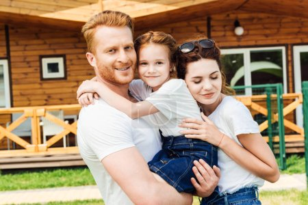 happy young family embracing in garden of wooden cottage