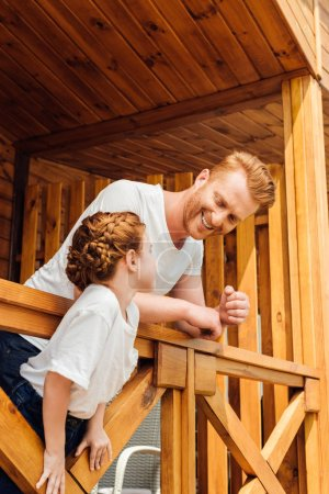 happy father and daughter spending time together on terrace of wooden cottage