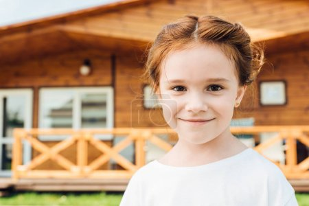 happy little child looking at camera in front of wooden cottage