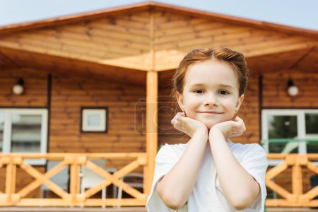 adorable little child looking at camera in front of wooden cottage