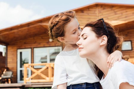 happy mother and daughter cuddling in front of wooden cottage