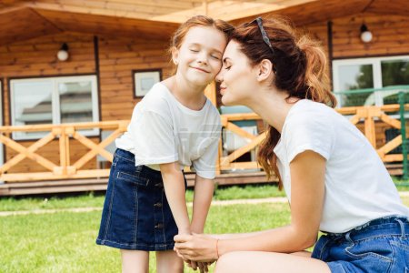 beautiful mother and daughter cuddling and holding hands in front of wooden cottage