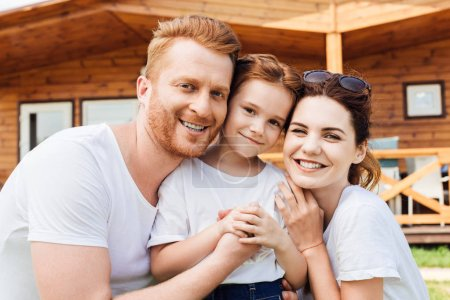 close-up shot of beautiful young family embracing in front of wooden cottage and looking at camera