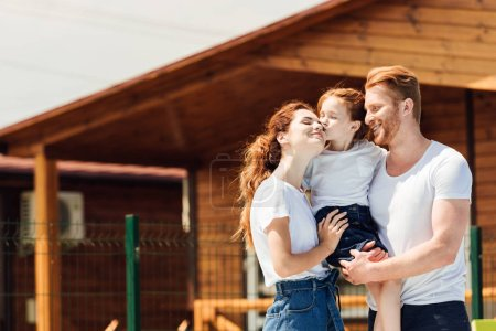 beautiful young family embracing in front of wooden cottage