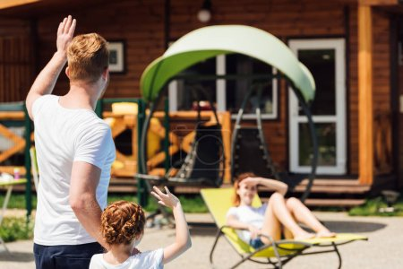 rear view of father and daughter waving to mother while she relaxing on sun lounger