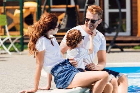 Photo for Smiling young family in white t-shirts and sunglasses sitting on poolside together - Royalty Free Image