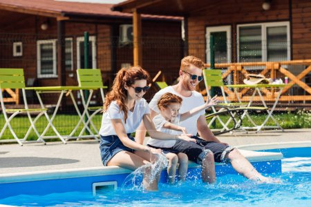 beautiful young family in white t-shirts and sunglasses sitting on poolside together