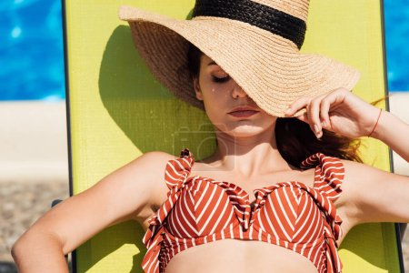 Photo for Close-up portrait of attractive young woman in straw hat and bikini relaxing on sun lounger at poolside - Royalty Free Image