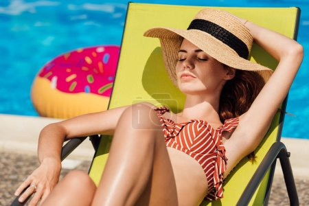 attractive young woman in straw hat relaxing on sun lounger at poolside
