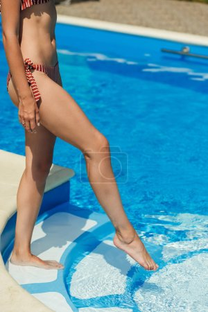 cropped shot of fit woman going into swimming pool