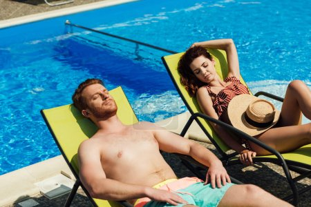 young couple tanning on sun loungers in front of swimming pool