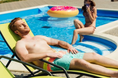 handsome young man tanning on sun lounger while his girlfriend sitting on poolside