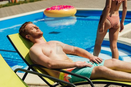 handsome young man tanning on sun lounger while his girlfriend going into swimming pool