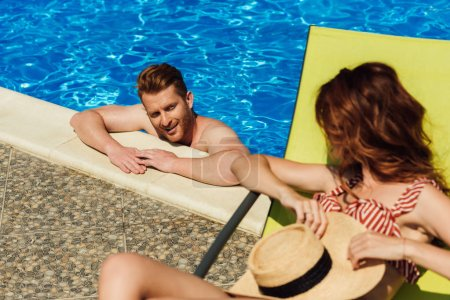 young man flirting with woman lying on sun lounger while swimming in pool
