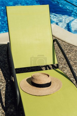 straw hat lying on sun lounger at poolside