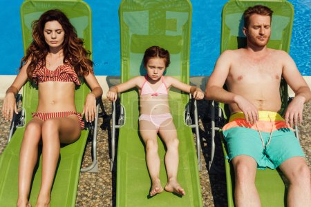 relaxed young family tanning on sun loungers together