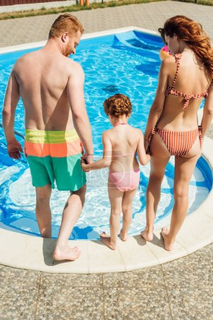 rear view of young family going into swimming pool