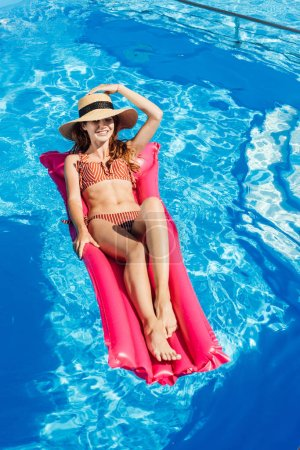 smiling young woman in straw hat and bikini  floating on inflatable mattress at swimming pool