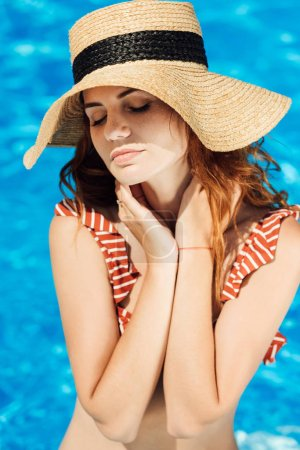close-up portrait of beautiful young woman in straw hat and bikini in front of swimming pool
