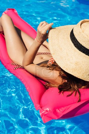 Photo for Young woman in straw hat and bikini  floating on inflatable mattress at swimming pool - Royalty Free Image