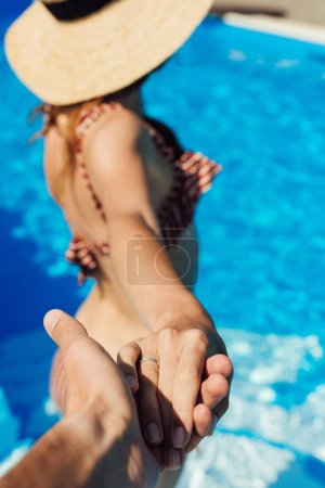cropped shot of man holding hand of young wife in swimming pool, follow me concept