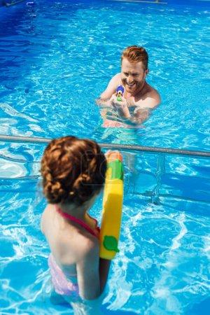 père et petite fille jouant avec des pistolets à eau dans la piscine