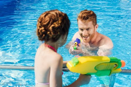 young father and daughter playing with water guns in swimming pool