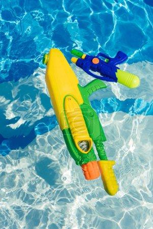 Bunte Wasserpistolen aus Plastik schwimmen im Schwimmbad