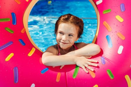 adorable little child with inflatable ring in shape of donut in swimming pool