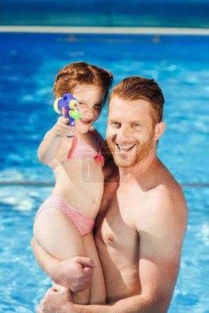 heureux père et fille avec pistolet à eau embrassant dans la piscine et regardant la caméra
