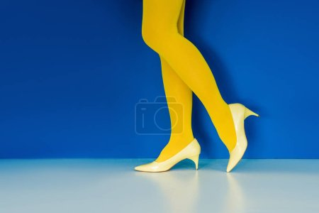 Cropped view of girl in yellow shoes and pantyhose on blue background