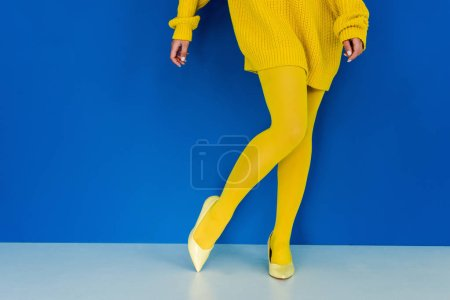 Cropped view of woman wearing yellow clothes and shoes posing on blue background