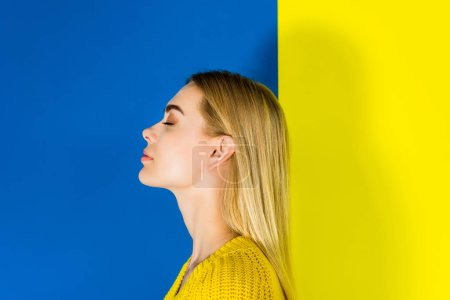 Portrait of blonde girl with closed eyes on blue and yellow background