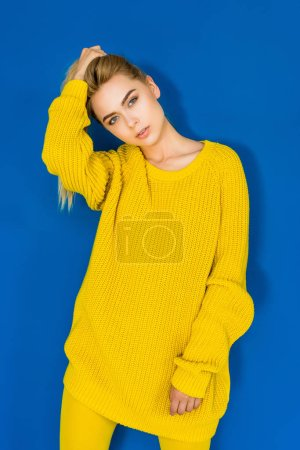 Elegant blonde woman in yellow sweater posing on blue background