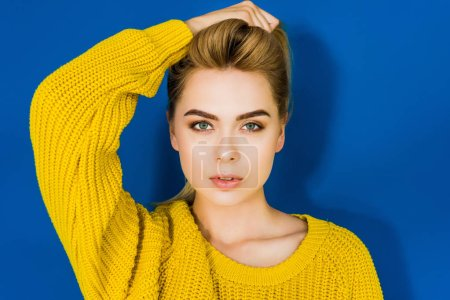 Female fashion model in yellow sweater posing on blue background