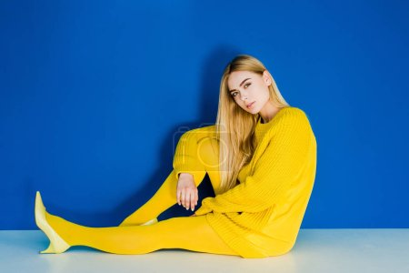 Female fashion model dressed in yellow sitting on floor on blue background