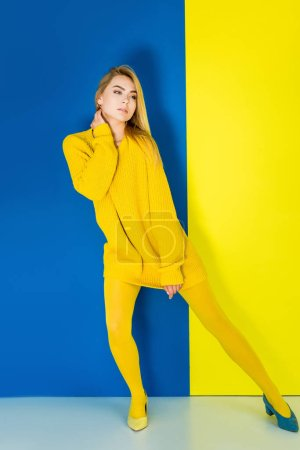 Female fashion model in yellow clothes and one blue shoe on blue and yellow background