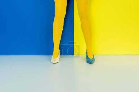 Cropped view of female legs in different shoes on blue and yellow background