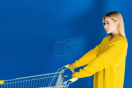 Photo for Attractive young girl pushing shopping cart on blue background - Royalty Free Image