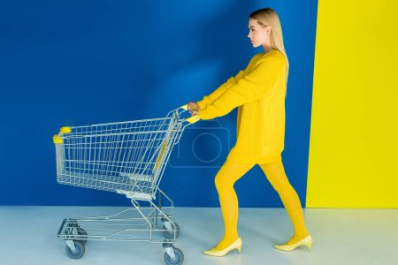 Elegant blonde woman pushing shopping cart on blue and yellow background