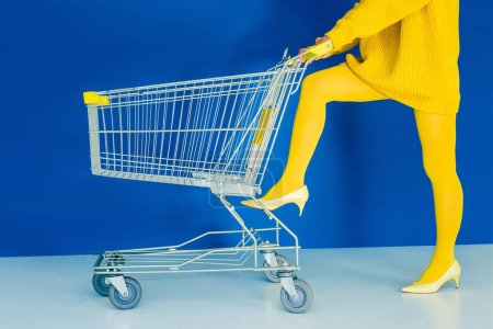Cropped view of woman leaning on shopping cart on blue background